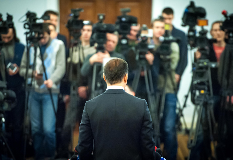A person facing the press pack of reporters and cameramen