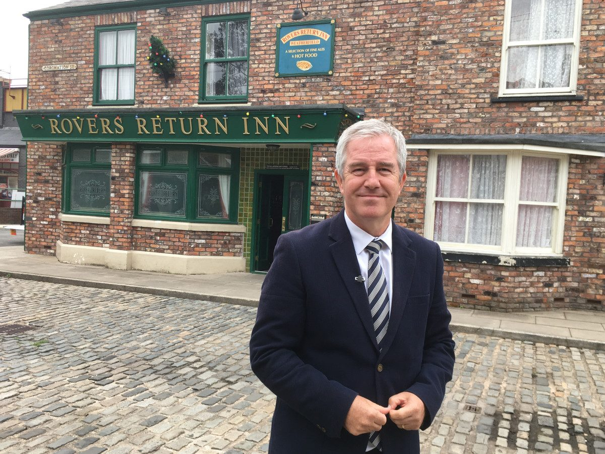 A colour photograph showing experienced media journalist Mike McCarthy reporting live from the set of ITV soap opera, Coronation Street